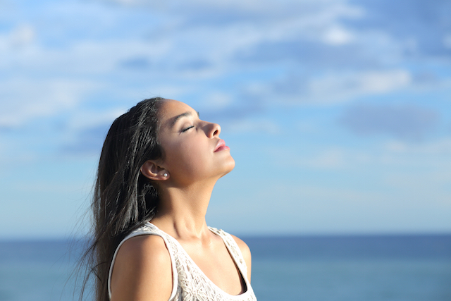 Beautiful arab woman breathing fresh air in the beach